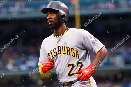 Pittsburgh Pirates' Andrew McCutchen smiles after scoring on an infield single by David Freese off Colorado Rockies starting pitcher Jeff Hoffman in the first inning of a baseball game, in Denver