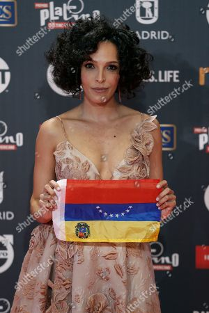Venezuelan actress Arlette Torres holds an upside-down Venezuelan flag as she poses for photographers before the Platino Awards ceremony in Madrid, . The Platino Awards honor cinema produced in Latin America, Spain and Portugal