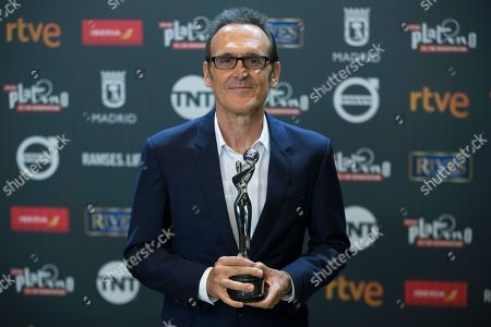 Spanish composer Alberto Iglesias poses for photographers after winning the best original music award during the Platino Awards ceremony in Madrid,. The Platino Awards honor cinema produced in Latin America, Spain and Portugal
