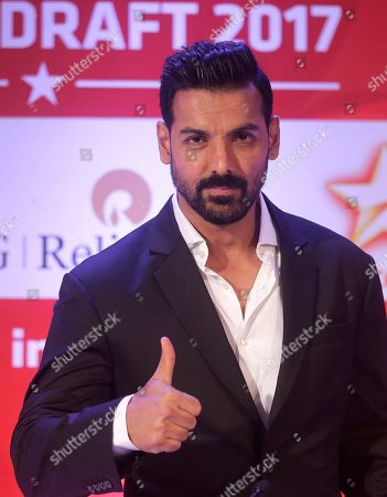Indian Super League's (ISL) North East United FC owner and Bollywood actor John Abraham gestures as he arrives to speak with media during the player draft of the ISL in Mumbai, India