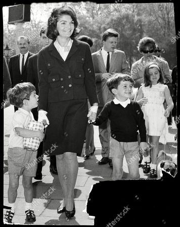 Stock Photo of Jackie Onassis With Her Son John Kennedy Jnr (with Loaf Of Bread) On Their Way To Feed The Ducks In Green Park London With Anthony Radziwell. Jacqueline Lee Bouvier Kennedy Onassis (died May 1994) Widow Of President John F. Kennedy And Shipping Magnate Aristotle Onassis. Jackie Kennedy