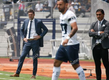 Pachuca's coach Diego Martin Alonso, left, and Puma's coach Francisco Palencia, right, watch from the sidelines during a Mexican soccer league match in Mexico City, . Pumas won the match 1-0