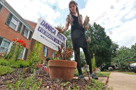 Democratic nominee for the House of Delegates 13th district seat, Danica Roem, places a campaign sign as she canvasses a neighborhood, in Manassas, Va. Roem is running against Del. Bob Marshall in the 13th House of Delegates District