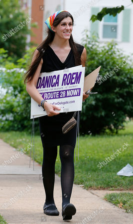 Democratic nominee for the House of Delegates 13th district seat, Danica Roem, brings campaign signs as she greets voters while canvasing a neighborhood, in Manassas, Va. Roem is running against Del. Bob Marshall in the 13th House of Delegates District