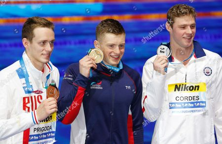 Britain's gold medal winner Adam Peaty is flanked by United States' silver medal winner Kevin Cordes, right, and Russia's bronze medal winner Kirill Prigoda after the ceremony for the men's 100-meter breaststroke final during the swimming competitions of the World Aquatics Championships in Budapest, Hungary