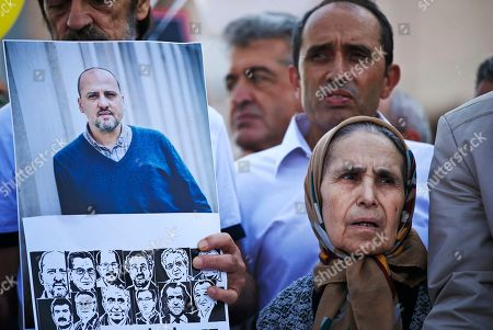 Flanked by a photograph of Cumhuriyet newspaper's investigative journalist Ahmet Sik, top left, and images of other defendants, left, Emine Yilmaz, 79, gathers outside a court in Istanbul, protesting against the trial of journalists and staff from the Cumhuriyet newspaper, accused of aiding terror organizations. Journalists and staff from the Turkish newspaper staunchly opposed to President Recep Tayyip Erdogan have gone on trial in Istanbul, accused of aiding terror organizations - a case that has added to concerns over rights and freedoms in Turkey