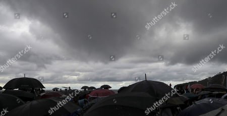Revellers with umbrellas attend the concert of Ernie Watts Quartet, under a heavy rain cloud, during the San Sebastian Jazz Festival in San Sebastian, Spain, 24 July 2017. The San Sebastian Jazz Festival runs from 20 to 25 July.