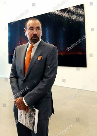 """Jorge Perez waits for reporters and guests to begin the private viewing of On the Horizon: Contemporary Cuban Art from the Jorge Perez Collection, at the Perez Art Museum in Miami. The piece behind Perez, """"Fire (America)"""" is by Teresita Fernandez"""