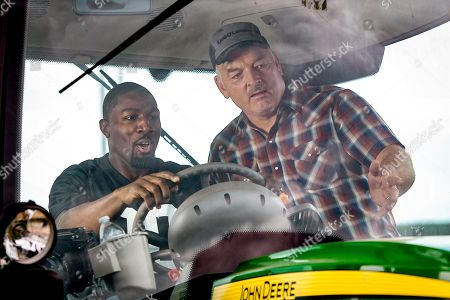 Stock Photo of Former Minnesota Vikings wide receiver Greg Jennings learns to drive a tractor for the Land O'Lakes Farm Bowl from Marvin Carrow at the Enchanted Dairy, in Little Falls, Minn