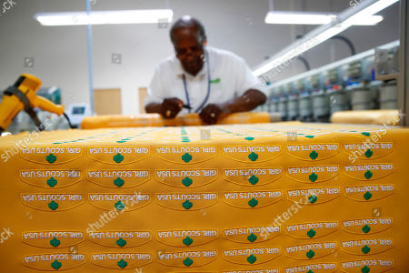 Jim Morris works on a sheet of Girl Scout patches at the Lion Brothers factory in Owings Mills, Md. Lion Brothers manufactures patches and badges for the Girl Scouts of the USA, including 23 new badges focused on science, technology, engineering and math