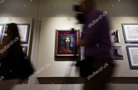 Journalists pass by a painting depicting actor Robert Powell as seen in Franco Zeffirelli's 1977 film 'Jesus of Nazareth' during a preview of the Franco Zeffirelli International Centre for the Performing Arts in the the late 17th century San Firenze Complex in Florence, . The center, besides its educational activities, brings together the entire artistic and cultural patrimony of the Italian director's almost 70-year career, including over ten thousand books from his personal library, thousands of professional documents and notes, designs, sketches, scripts, screenplays and storyboards, as well as a substantial collection of photographs of his works from the post-war years to present days. The center will open to the public on Sept. 1