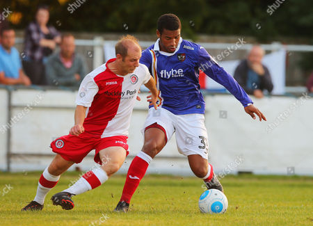 Reuben Reid of Exeter City battles for the ball with Luke Roberts of Poole Town during the Pre Season Match between Poole Town and Exeter City at Tatnam Stadium, Poole, Dorset on 25 July 2017.