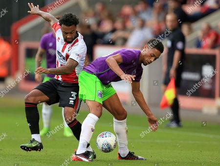 Zak Vyner of Bristol City holds off Jordan Cranston of Cheltenham Town