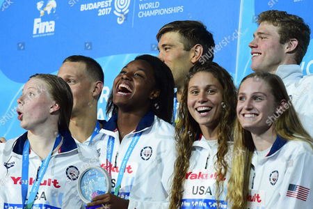 US swimmers (front row, L-R) Lilly King, Simone Manuel, Mallory Comerford, and Kelsi Worrell; (back, L-R) Caeleb Remel Dressel, Matt Grevers, and Kevin Cordes celebrate on the podium after winning the gold medal in the mixed 4x100m Medley Relay final during the 17th FINA Swimming World Championships in the Duna Arena in Budapest, Hungary, 26 July 2017.
