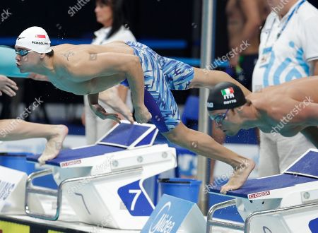 Singapore's Joseph Schooling, left, and Italy's Luca Dotto start a men's 100-meter freestyle heat during the swimming competitions of the World Aquatics Championships in Budapest, Hungary