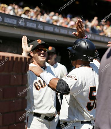San Francisco Giants' Miguel Gomez, right, is greeted in the dugout after scoring the Giants' second run in the seventh inning of a baseball game against the Pittsburgh Pirates, in San Francisco. San Francisco won the game 2-1