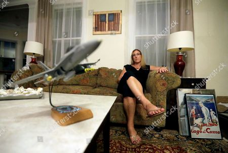 """Stock Image of A model F18 jet sits on a coffee table as Alaina Kupec poses for a photograph at her home, in Orange, N.J. Kupec, a transgender woman who worked with pilots who flew F18 jets while serving as a Navy intelligence officer from 1992 until 1995, said she felt """"heartbreak"""" after she heard about Trump's Twitter pronouncement banning transgender people from military service. The 48-year-old publicly transitioned to life as a woman in 2013"""