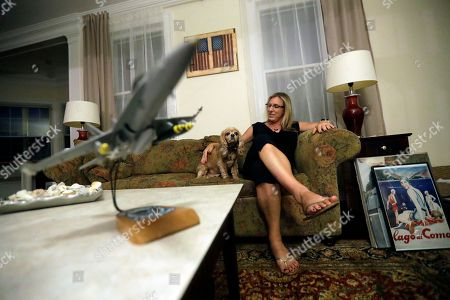 """Stock Picture of A model F18 jet is displayed on a coffee table as Alaina Kupec sits with her dog Pearce at her home, in Orange, N.J. Kupec, a transgender woman who worked with pilots who flew F18 jets while serving as a Navy intelligence officer from 1992 until 1995, said she felt """"heartbreak"""" after she heard about Trump's Twitter pronouncement banning transgender people from military service. The 48-year-old publicly transitioned to life as a woman in 2013"""