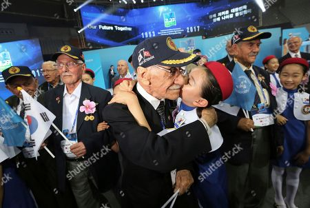 Turkish Korean War veteran Osman Cucer, center, is kissed by South Korean elementary school student Han Ji-min during a commemorative ceremony marking the 64th anniversary of the Armistice Agreement and U.N. Forces Participation in the Korean War in Seoul, South Korea