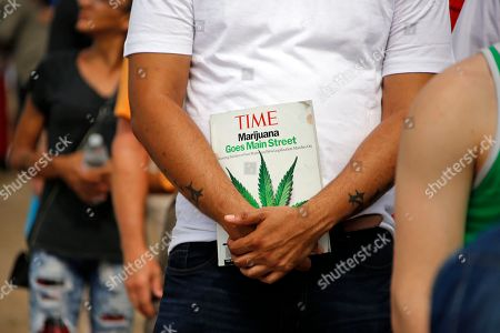 Michael Cole of Clairton, Pa., holds a Time magazine while waiting on line in downtown McKeesport, Pa., to attend a Medical Marijuana Job Fair, . Named as one of Pennsylvania's first grower-processor licensees for medicinal cannabis, PurePenn, based in McKeesport, Pa., will hire in the next ten months up to 50 full-time employees including; sales managers; cultivation managers;cultivators; packagers; and lab supervisors
