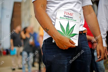 Michael Cole, of Clairton, Pa., holds a Time magazine while waiting on line in downtown McKeesport, Pa., to attend a Medical Marijuana Job Fair, . Named as one of Pennsylvania's first grower-processor licensees for medicinal cannabis, PurePenn, based in McKeesport, Pa., will hire in the next ten months up to 50 full-time employees including; sales managers; cultivation managers;cultivators; packagers; and lab supervisors