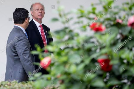 Rep. Dan Donovan, R-N.Y., right, walks through the colonnade from the West Wing into the White House in Washington