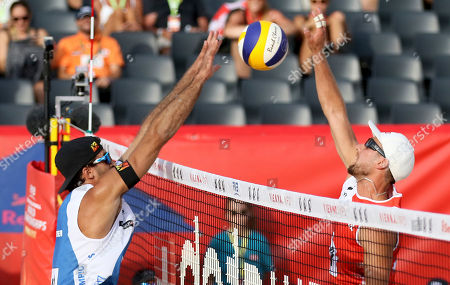 Italy's Alex Ranghieri, left, plays the ball against Poland's Grzegorz Fijalek during the Men's pool play at the Beach Volleyball Worlds Championships in Vienna, Austria