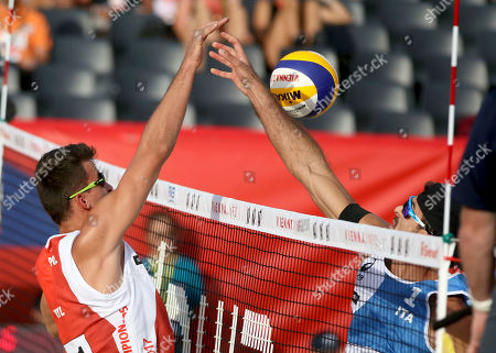 Stock Picture of Poland's Michal Bryl, left, plays the ball against Italy's Alex Ranghieri, during the Men's pool play at the Beach Volleyball Worlds Championships in Vienna, Austria