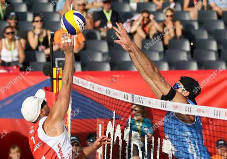 Poland's Grzegorz Fijalek, left, plays the ball against Italy's Alex Ranghieri during the Men's pool play at the Beach Volleyball Worlds Championships in Vienna, Austria