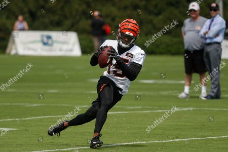 Cincinnati Bengals wide receiver John Ross III (15) runs a play as Bengals owner Mike Brown, second from right, watches from the sidelines during an NFL football training camp, in Cincinnati