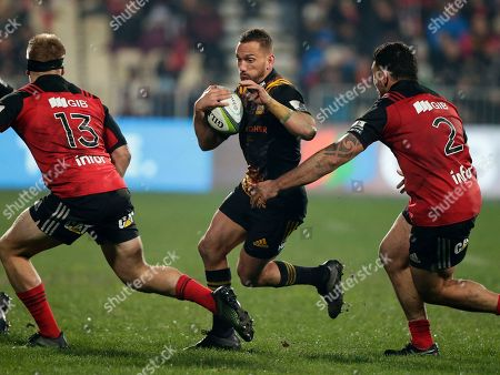 Chiefs Aaron Cruden runs between Crusaders Jack Goodhue, left, and Codie Taylor during their Super Rugby semifinal in Christchurch, New Zealand