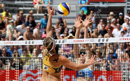 Germany's Isabel Schneider, left, plays the ball to U.S. Emily Day, during the Women's pool play at the Beach Volleyball World Championships in Vienna, Austria