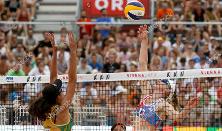 Stock Photo of Brazil's Talita Da Rocha Antunes plays the ball to United States's Emily Day, from left, during the Women's pool play at the Beach Volleyball World Championships in Vienna, Austria