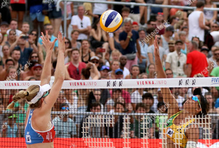 Brazil's Larissa Franca Maestrini plays the ball to United States's Emily Day, from left, during the Women's pool play at the Beach Volleyball World Championships in Vienna, Austria