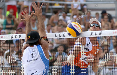 Stock Image of Italy's Alex Ranghieri plays the ball to Netherland's Robert Meeuwsen, from left, during the men's pool play at the Beach Volleyball World Championships in Vienna, Austria