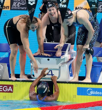 United States' Simone Manuel, bottom, and her teammates, top from left, Kathleen Baker, Lilly King and Kelsi Worrell celebrate after setting a new world record in the women's 4x100-meter medley relay during the swimming competitions of the World Aquatics Championships in Budapest, Hungary