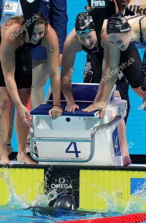 Stock Image of United States' Simone Manuel, bottom, and her teammates, top from left, Kathleen Baker, Lilly King and Kelsi Worrell celebrate after setting a new world record in the women's 4x100-meter medley relay during the swimming competitions of the World Aquatics Championships in Budapest, Hungary