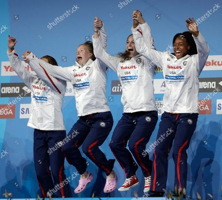 United States' gold medal winners Kathleen Baker, Lilly King, Kelsi Worrell and Simone Manuel, from left, jump onto the podium after setting a new world record in the women's 4x100-meter medley relay final during the swimming competitions of the World Aquatics Championships in Budapest, Hungary