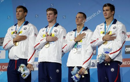 United States' gold medal winners Matt Grevers, Kevin Cordes, Caeleb Dressel and Nathan Adrian, from left, listen to the national anthem during the ceremony for the men's 4x100-meter medley relay final during the swimming competitions of the World Aquatics Championships in Budapest, Hungary