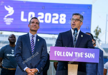 Los Angeles Mayor Eric Garcetti listens as L.A. Olympic Committee leader Casey Wasserman speaks during a press conference to make an announcement for the city to host the Olympic Games and Paralympic Games 2028, at StudHub Center in Carson, outside of Los Angeles, Calif