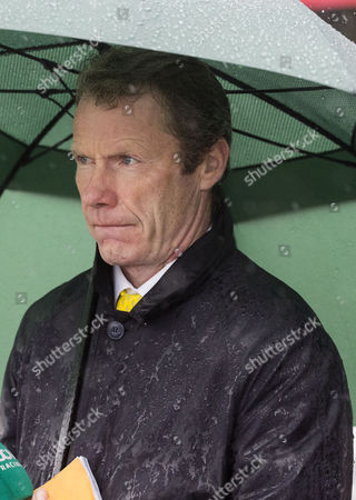 ITV presenter Mick Fitzgerald braves the heavy rain on the second day of the Glorious Goodwood Festival to watch the first race.