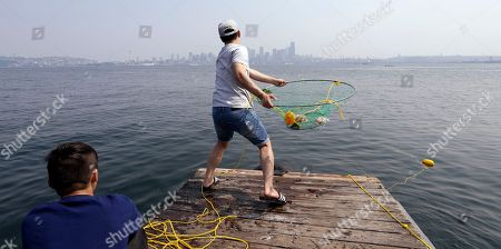 Stock Photo of Justin Lin prepares to throw a crab net into Puget Sound in view of downtown Seattle, cloaked in a haze of smoke from fires raging in British Columbia that swept down into the Puget Sound region, in Seattle. An excessive heat warning for the area continues through Friday evening, as unusually hot weather will bring temperatures in the 90's