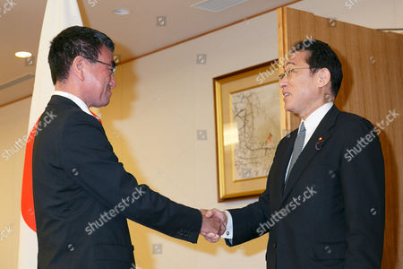 (L to R) Japan's new Foreign Minister Taro Kono shakes hands with his predecessor Fumio Kishida during a transfer ceremony
