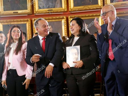 Members of Venezuela's Constituent Assembly, Celia Flores, left, Diosdado Cabello, second left, Carmen Melendez, second right and Jorge Rodriguez, celebrate after being sworn-in, inside Venezuela's National Assembly in Caracas, Venezuela, . Venezuelan President Nicolas Maduro is heading toward a showdown with his political foes, after seating a loyalist assembly that will rewrite the country's constitution and hold powers that override all other government branches