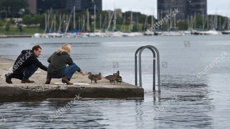 Ricky, left, and Bethany try to feed a group of ducklings, in Chicago. Autumn like temperature arrives with winds blowing at 18mph, coolest temperature in months. Weather forecast project a high of 68 and will drop to a low of 59 later in the evening