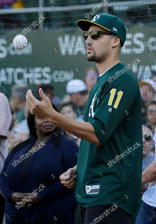 Golden State Warriors basketball player Klay Thompson before throwing out a ceremonial first pitch before a baseball game between the Oakland Athletics and the San Francisco Giants in Oakland, Calif