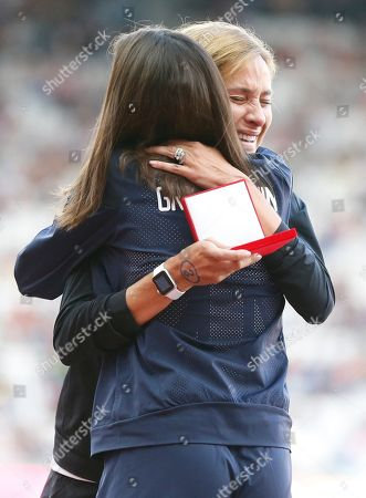 Kara Goucher of the United States embraces Britain's Joanne Pavey during a ceremony at the World Athletics Championships in London,. Goucher, silver, and Pavey, bronze, received medals for the Women's 10,000m at the World Championships in Osaka in 2007 which follows the disqualification of the results of the original medallists after their sanction for anti-doping rule violations