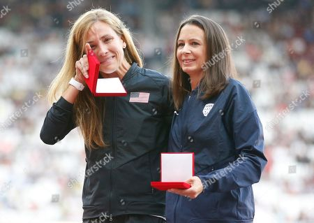 Kara Goucher of the United States, left, wipes away a tear as she stands with Britain's Joanne Pavey during a ceremony at the World Athletics Championships in London,. Goucher, silver, and Pavey, bronze, received medals for the Women's 10,000m at the World Championships in Osaka in 2007 which follows the disqualification of the results of the original medallists after their sanction for anti-doping rule violations