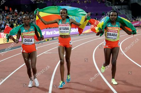 Stock Photo of Ethiopia's gold medal winner Almaz Ayana is accompanied by her teammates silver medal winner Tirunesh Dibaba, right, and Dera Dida, left, as she celebrates after the women's 10,000 meter final during the World Athletics Championships in London