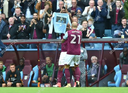 Gabriel Agbonlahor of Aston Villa scores the opening goal 1-0 and celebrates by holding up a shirt wishing a fellow player well